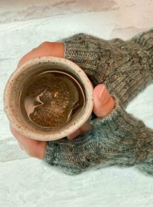 Two hands clad in greyish-green knitted mitts with cables, holding a mug filled with tea. The knitting pattern is by Kate Atherley and can be found in Nomadic Knits creative knitting magazine