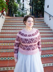 Mona Zillah modeling her Sakura sweater in front of brightly colored tile stairs. Sakura was knit using The Plucky Knitter indie dyed yarn; the pattern is available in Nomadic Knits creative knitting magazine