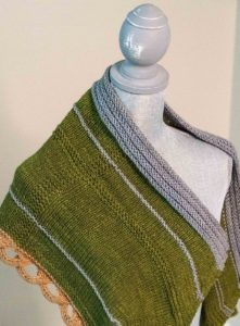 Green, silver and tan shawl draped over a dressform; knitting pattern by michelle grace, aka knitdraper; shown in Why Knot Fibers indie dyed yarn; found in Nomadic Knits creative knitting magazine