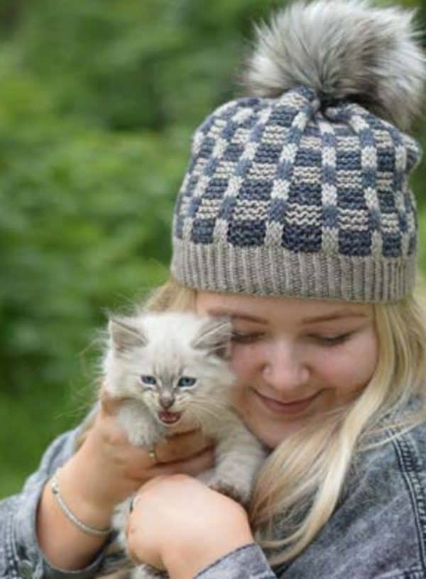 Blond haired young woman holding a grey kitten, wearing the higgins lake hat with a faux fur pom pom; knitting pattern by Jodi Brown of Grocery girls knit, available in Nomadic Knits knitting magazine subscription