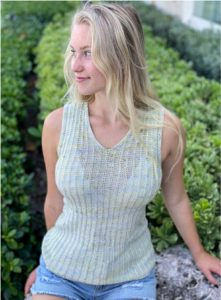 Young blond woman looking over her right shoulder. She is wearing the Mile Road tank, a knitting pattern by tina tse, knit in indie dyed yarn by Hawari Bazaar. Mile Road tank can be found in Nomadic Knits knitting magazine. Picture demonstrates negative ease in knitting.