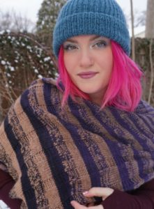 White woman with incredible hot pink hair wearing a blue knit hat and modeling a striped purple and tan shawl; indie yarn dyer Twisted Fiber Art; knitting pattern by Rizzaknits, found in Nomadic Knits creative knitting magazine