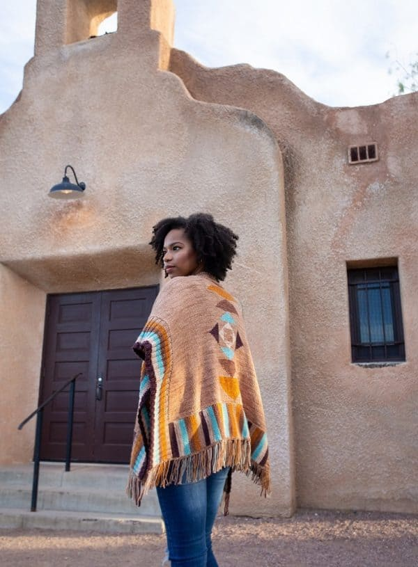 Light skinned Black woman in front of an adobe style building, wearing a beautiful Ruana in a pale tan with brown, eggplant, turquoise and white colorwork