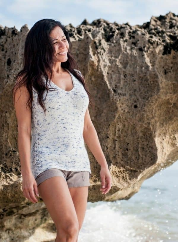 Brunette woman on the beach in front of a huge jagged rock. She is wearing a white with blue speckles knitted tank and tan shorts. The knitting pattern is Safe Haven and is shown in Emma's Yarn, indie dyed yarn. It can be found in issue one of Nomadic Knits creative knitting magazine.