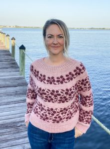 Sakura sweater in plucky knitter hand dyed yarn, worn by a blond woman on a dock over a river; the sweater is pink with burgundy flowers; knitting pattern found in Nomadic Knits creative knitting magazine