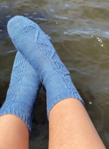 Two feet hanging over river water, wearing Shoreline socks by Tracie Millar of the Grocery Girls knit; Indie yarn dyer The Plucky Knitter in light blue was used for the knitting pattern, which is found in Nomadic Knits creative knitting magazine.