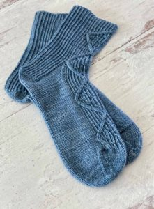 Two blue socks in indie dyed yarn from the Plucky Knitter, in a delicately cabled knitting design from Tracie Millar of Grocery Girls knit, knitting pattern found in Nomadic Knits creative knitting magazine