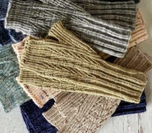 stack of six pairs of Mackinac Mitts, a knitting pattern by kate atherley, shown in six different colorways from indie yarn dyers in michigan. The mitts are featured in Nomadic Knits knitting magazine subscription