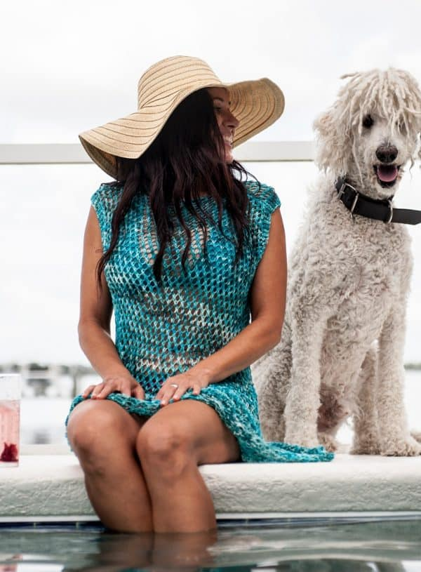 Brunette woman in a floppy straw hat sitting poolside with a cocktail and a derpy white poodle. She is wearing a turquoise mesh-looking knitted swim coverup. The knitting pattern can be found in issue one of Nomadic Knits creative knitting magazine.