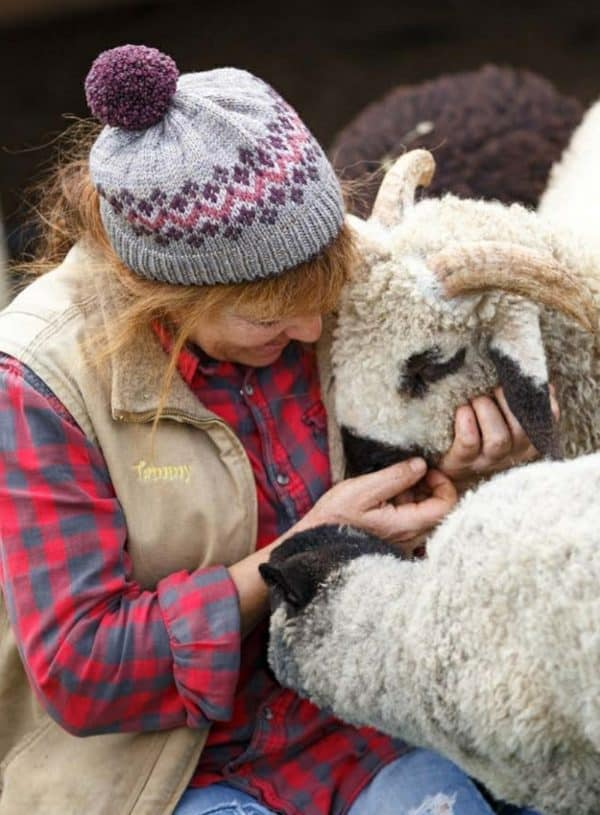 Tammy white from wing and a prayer farm wearing a fair isle knit hat knit in wonderland yarns, with a pom pom. Tammy has a red braid, a red plaid shirt, and a brown insulated vest. She is cuddling her valois blacknose sheep.
