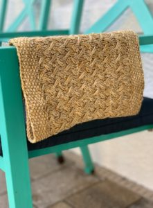 Third coast cowl draped over a chair; a golden yellow from indie yarn dyer UPNorth; knitting pattern by Laura Dobratz and found in Nomadic Knits creative knitting magazine