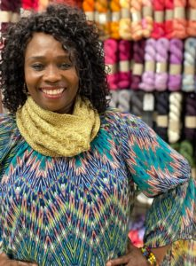 Black woman standing in front of a wall of yarn wearing a bright colored shirt and a golden yellow cowl; knitting pattern by Laura Dobratz; indie yarn dyer UPNorth yarns; found in creative knitting magazine Nomadic Knits