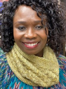 Beautiful dark skinned Black woman wearing a golden yellow knitted cowl; pattern in indie dyed yarn in creative knitting magazine