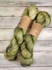 Two twisted hanks of pale green tonal yarn; colorway is Meadow from Indie yarn dyer This Craft or That, used in Agate Falls knitting pattern in Nomadic Knits knitting magazine subscription