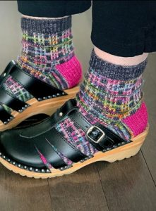 Tracie Millar of Grocery Girls Knit, view of her feet, wearing black strappy clogs and hand knit socks in grey, pink, yellow tartan
