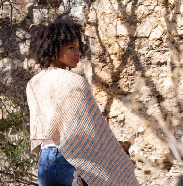Woman wrapped in a pastel striped shawl. The knitting pattern is by Jessica Anderson using indie dyed yarn and found in issue three of Nomadic Knits creative knitting magazine
